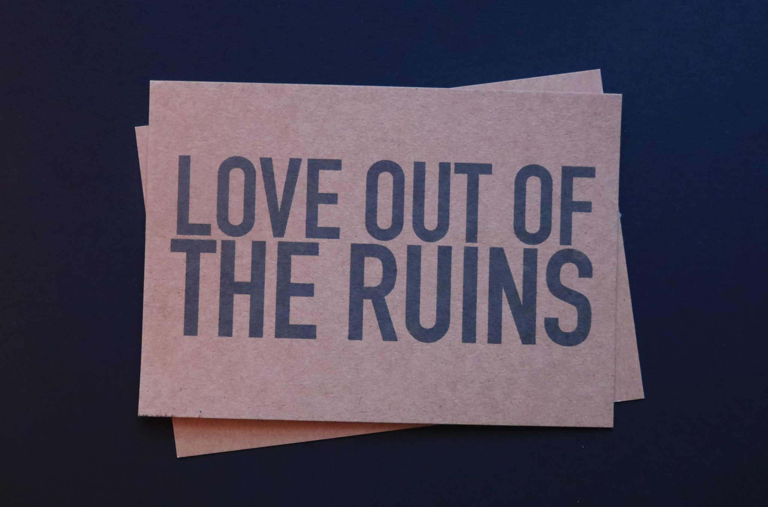 Postcard with the words Love Out of the Ruins